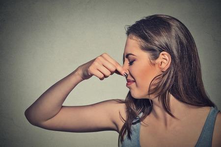 olfato: Side tiro en la cabeza mujer perfil retrato pellizca la nariz con los dedos se ve con disgusto distancia algo apesta mala situación olor aislado fondo de la pared gris. Expresión de la cara humana de reacción lenguaje corporal