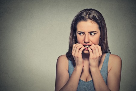 hesitant: Closeup portrait young unsure hesitant nervous woman biting her fingernails craving for something or anxious, isolated on gray wall background. Negative human emotions facial expression feeling