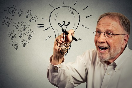 investment ideas: Senior excited businessman has an idea drawing a lightbulb with pen