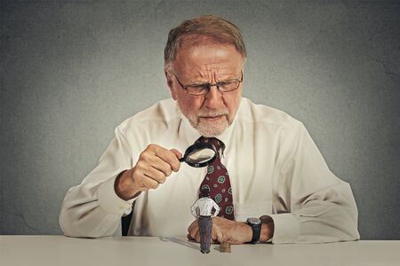 evaluating: Curious corporate senior businessman skeptically meeting looking at small employee worker through magnifying glass isolated office grey wall background. Human face expression, attitude, perception
