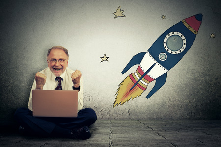 rocket man: Excited senior man with high risky goals targets working on laptop computer on a starry wall background. Successful adventure concept Stock Photo