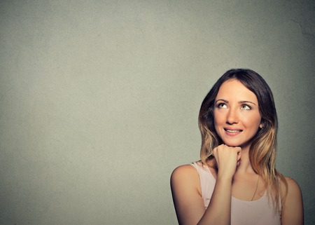making up: Closeup portrait happy young woman thinking dreaming has ideas looking up isolated on gray wall background copy space. Positive human emotion feeling life perception. Decision making process concept.