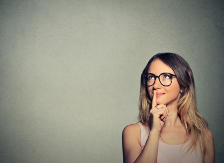 mujer pensando: Retrato del primer mujer joven feliz pensando sueño tiene ideas mirando hacia arriba aislados en la pared gris copia espacio de fondo. Positivo emoción humana sintiendo percepción vida. Toma de decisiones concepto de proceso. Foto de archivo