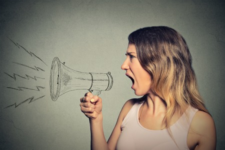 Portrait angry screaming young woman holding megaphone isolated on grey wall background. Negative face expression emotion feelings. Propaganda, breaking news, power, social media communication concept