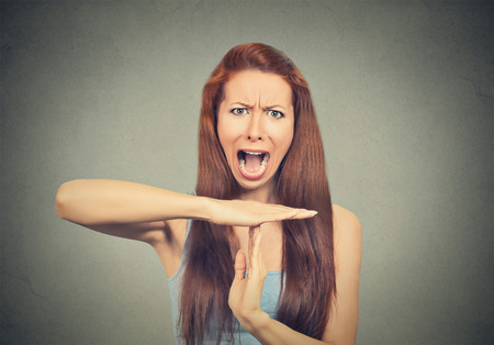 out time: Young woman showing time out hand gesture, frustrated screaming to stop isolated on grey wall background. Too many things to do. Human emotions face expression reaction