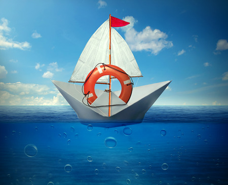 afloat: Rescue situation financial bailout support concept. Paper boat safeguarded by lifebuoy ring in a middle of ocean Stock Photo
