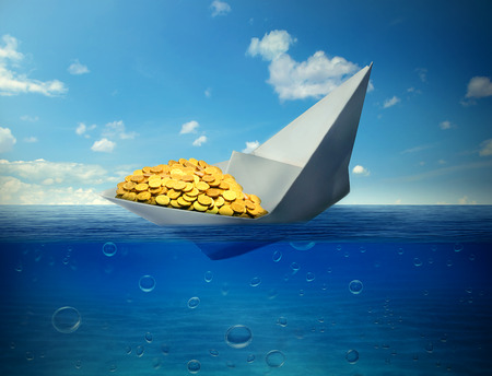 lower value: sinking paper boat transporting gold as a symbol of worldwide declining commodity prices Stock Photo