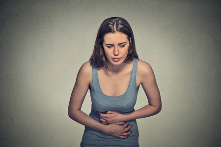 bowel: Portrait young woman hands on stomach having bad aches pain isolated on gray wall background. Food poisoning, influenza, cramps. Negative emotion facial expression reaction health issues problems Stock Photo