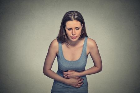 expresion corporal: Retrato de mujer joven manos en el estómago después de haber mal dolor dolores aislados sobre fondo gris de la pared. La intoxicación alimentaria, la gripe, calambres. Emoción negativa expresión facial problemas de salud reacción problemas