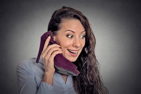 shoes woman: Headshot young surprised woman holding high heeled shoe in her hand as a phone isolated on gray wall background. Human face expression emotion feelings reaction Stock Photo