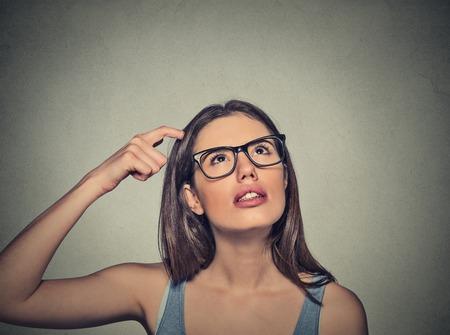 expresiones faciales: Retrato del primer mujer joven rascarse la cabeza, pensando soñando profundamente en algo mirando hacia arriba aislados en el fondo gris de la pared. Humanos faciales expresiones, emociones, sentimientos, signos, símbolos Foto de archivo