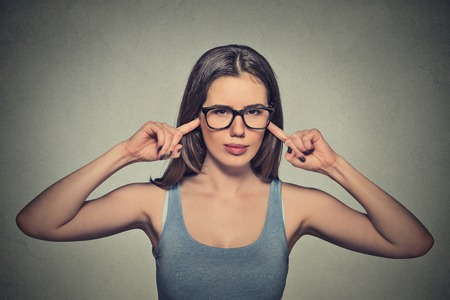 isolated on gray: Portrait young angry unhappy woman with glasses plugging ears with fingers looking at you annoyed loud noise giving her headache ignoring isolated gray background. Negative emotion perception attitude Stock Photo