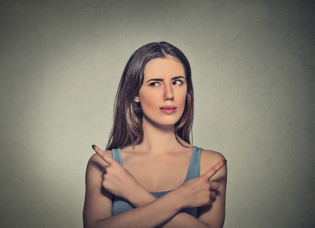 ambiguous: Portrait confused young woman pointing in two different directions not sure which way to go in life. Negative emotion facial expression feeling body language perception