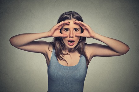 isolated on gray: Closeup portrait, headshot young woman, peeking through fingers like binoculars  surprised shocked searching something looking into future isolated gray wall background. Human face expression emotion