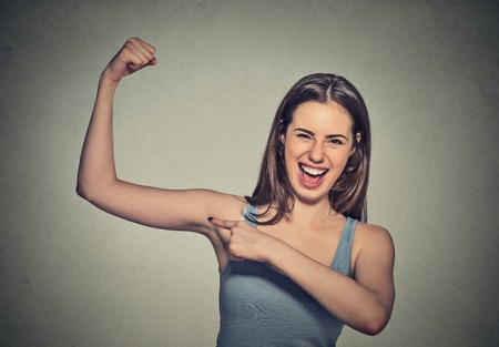 facial muscles: Closeup portrait beautiful fit young healthy model woman flexing muscles showing her strength isolated on grey wall background. Positive emotion facial expression feeling attitude perception wellbeing