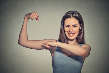 muscle girl: Closeup portrait beautiful fit young healthy model woman flexing muscles showing her strength isolated on grey wall background. Positive emotion facial expression feeling attitude perception wellbeing