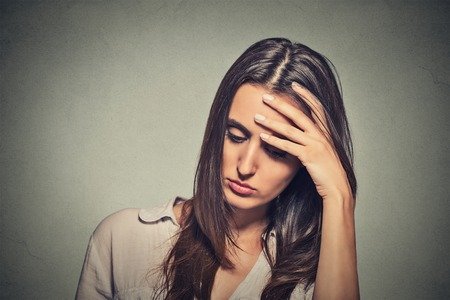 tired woman: portrait stressed sad young woman looking down isolated on gray wall background Stock Photo