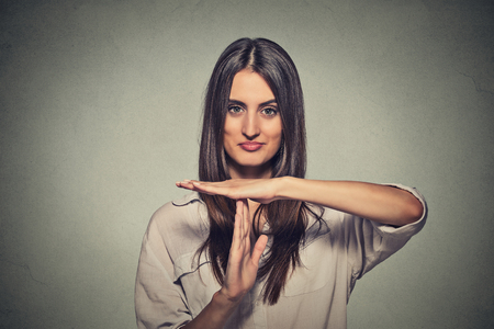 positive: Closeup portrait, young, happy, smiling woman showing time out gesture with hands isolated on gray wall background. Positive human emotion facial expressions, feeling body language reaction, attitude