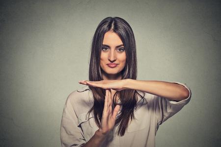 actitud: Primer retrato, joven, feliz, sonriente mujer que muestra el tiempo de espera gesto con las manos aisladas en el fondo de la pared gris. Expresiones faciales de emoci�n humana positivos, sinti�ndose reacci�n lenguaje corporal, actitud
