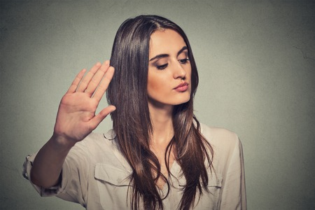 Close-up portret jonge geërgerd boze vrouw met slechte houding geven bespreking aan de hand gebaar met palm naar buiten geïsoleerde grijze muur achtergrond. Negatieve menselijke emotie gezichtsuitdrukking gevoel lichaamstaal