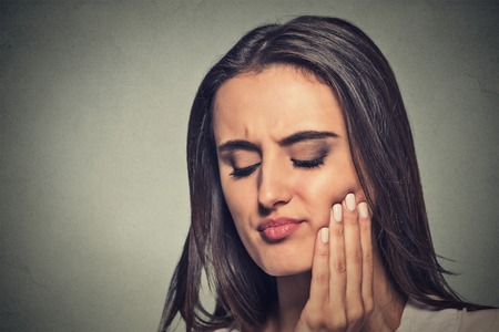 periodontal: Closeup portrait young woman with sensitive toothache crown problem about to cry from pain touching red area outside mouth with hand isolated gray background. Negative emotion face expression feeling Stock Photo