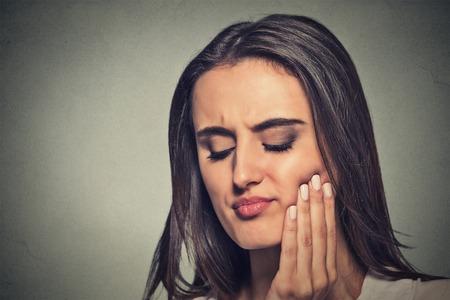 dolor de muelas: Primer retrato de mujer joven con corona sensible problema de muelas a punto de llorar de dolor de tocar área roja fuera de la boca con la mano aislada fondo gris. La emoción negativa sensación expresión de la cara