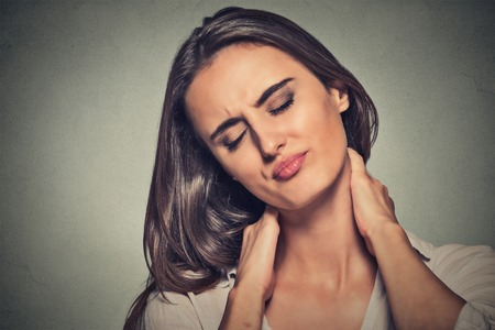 Back and spine disease. Closeup portrait tired woman massaging her painful neck isolated on gray wall background. Face expression