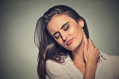 'head and shoulders': Back and spine disease. Closeup portrait tired woman massaging her painful neck isolated on gray wall background. Face expression