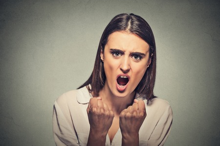insult: Closeup portrait angry frustrated woman screaming isolated on gray wall background. Negative emotion, feelings Stock Photo