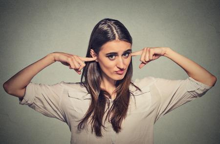 enchufe: Retrato del primer joven mujer infeliz enojado con los oídos cerrados mirarte molesto por ruido fuerte dando su dolor de cabeza ignorando aislado sobre fondo gris de la pared. Actitud percepción emoción negativa