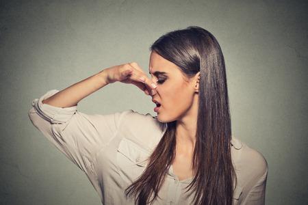 expresion corporal: Side tiro en la cabeza mujer perfil retrato pellizca la nariz con los dedos se ve con disgusto distancia algo apesta mala situación olor aislado fondo de la pared gris. Expresión de la cara humana de reacción lenguaje corporal