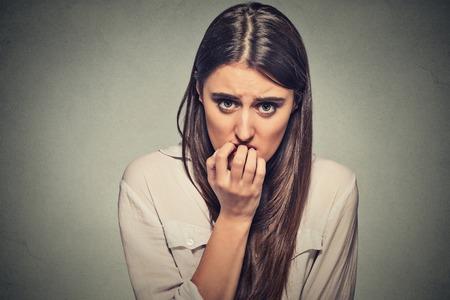 ansiedad: Retrato del primer joven inseguro vacilante mujer nerviosa mordiéndose las uñas antojo por algo o ansiosos, aislados sobre fondo gris de la pared. Emociones humanas negativas sensación de la expresión facial Foto de archivo