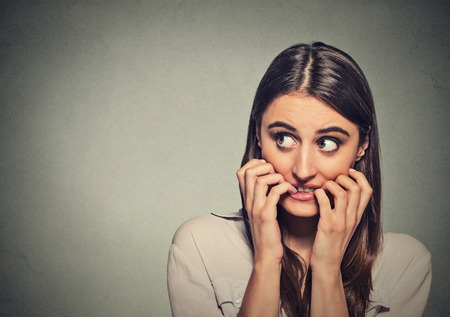 Closeup portrait young unsure hesitant nervous woman biting her fingernails craving for something or anxious, isolated on gray wall background. Negative human emotions facial expression feeling