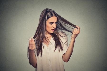vrouwen: Close ongelukkige gefrustreerde jonge vrouw verrast ze verliest haar terugwijkende haarlijn. Grijze achtergrond. Menselijk gezicht meningsuiting emotie. Beauty kapsel concept