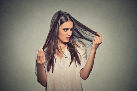 mujeres: Sorprendi� Primer infeliz mujer joven frustrado que est� perdiendo el pelo, rayita del retroceso. Fondo gris. Emoci�n expresi�n humana. Concepto de la belleza del peinado