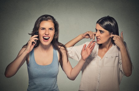 pissed off: Portrait two women loud, obnoxious rude woman talking loudly on cell phone, girl next to her pissed off closes ears having headache Isolated gray background. Negative emotion facial expression feeling