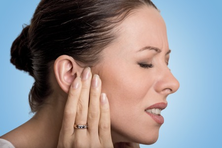 listening ear: Tinnitus. Closeup up side profile sick young female having ear pain touching her painful head isolated on blue background