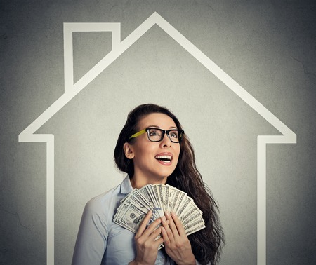 dollaro: a casa, i soldi, la gente il concetto. Giovane di successo felice business woman holding denaro contante dollaro in mano su casa e sfondo grigio muro