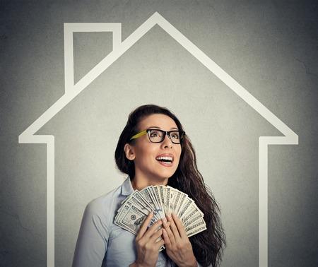 cash: casa, el dinero, la gente concepto. Sonriente joven mujer de negocios exitosa celebración de dinero en efectivo feliz dólar en la mano sobre la casa y la pared de fondo gris