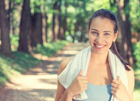 Portrait young attractive smiling fit woman with white towel resting after workout sport exercises outdoors on a background of park trees. Healthy lifestyle well being wellness happiness concept. Stock Photo