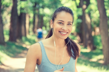 woman young: Portrait running young woman. Female runner jogging during outdoor workout in park on spring summer day. Beautiful fit girl. Attractive fitness model outdoors. Weight loss healthy lifestyle concept Stock Photo