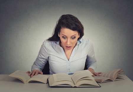 book club: Portrait young shocked woman sitting at desk with many opened books reading isolated grey wall background. Funny face expression emotion feelings problem perception reaction