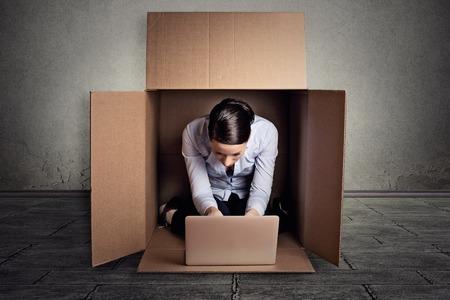 discriminacion: Primer joven empresaria escondiéndose sentado en la caja de cartón de trabajo en la computadora portátil