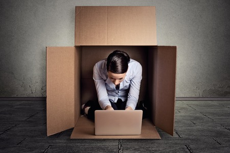 discriminacion: Primer joven empresaria escondi�ndose sentado en la caja de cart�n de trabajo en la computadora port�til