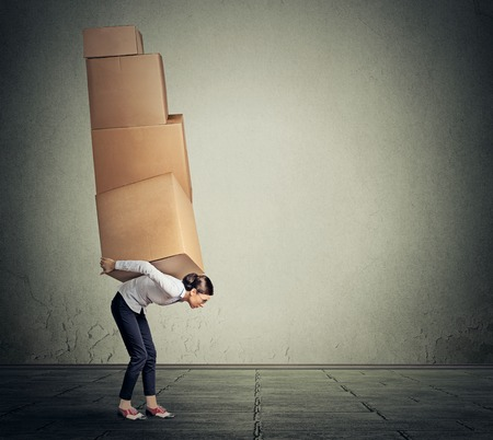 girl holding carrying several boxes on her back in equilibrium Stock Photo