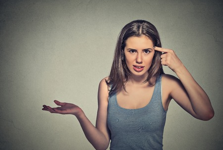Closeup portrait of angry mad young woman gesturing with her finger against temple asking are you crazy? Isolated on gray wall background. Negative emotions facial expression feeling body language