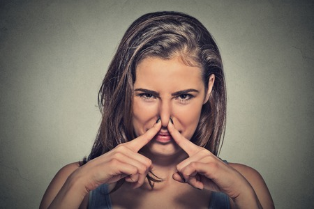 body language: Closeup portrait headshot woman pinches nose with fingers hands looks with disgust something stinks bad smell situation isolated on gray wall background. Human face expression body language reaction