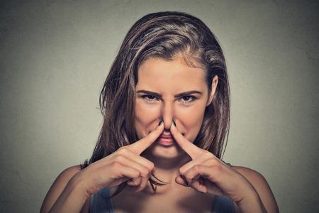 expresion corporal: Primer Headshot de la mujer del retrato pellizca la nariz con los dedos de las manos se ve con algo disgusto apesta situación olor mal aisladas sobre fondo gris de la pared. Expresión de la cara humana de reacción lenguaje corporal