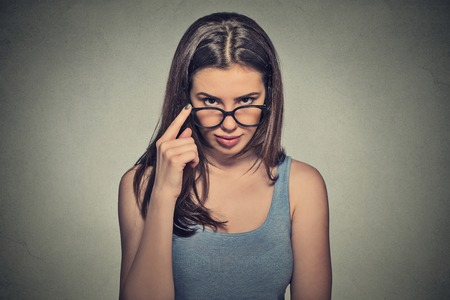 ego: Headshot angry bitchy serious woman with glasses skeptically looking at you isolated on gray wall background. Human face expression, body language, attitude, perception, vision