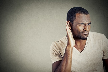 cochlear: Closeup portrait of handsome young guy trying to secretly listen in on a conversation and not pleased by what he hears isolated on gray wall background